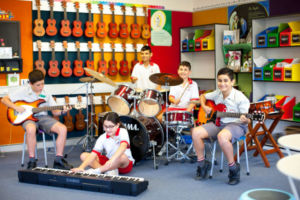 Group of students playing musical instruments in music room