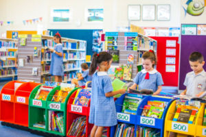 Students looking through books while others read in a bright, colourful library