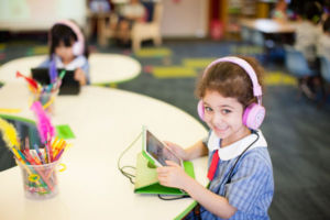 Young student using tablet and wearing headphones smiling