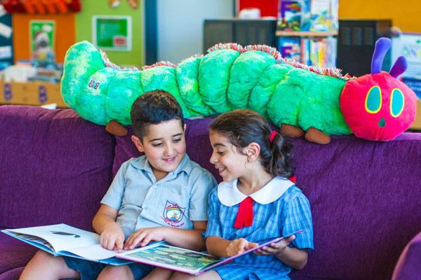 Two students smiling and reading a book together on a couch