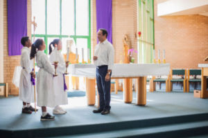 Three students in robes standing at the altar with the John the Baptist parish priest