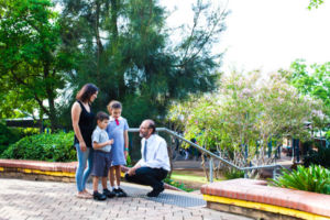 Mother with her two children talking with the principal outside