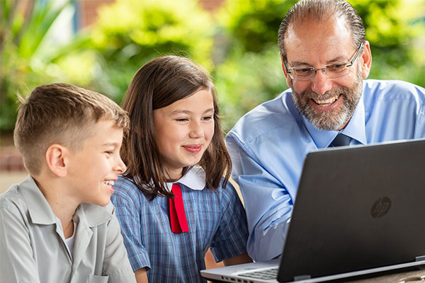 John the Baptist Catholic Primary School Bonnyrigg Heights Principal Tony Lo Casio working with two students at a computer