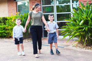Mother and two sons walking by front office of John the Baptist Catholic Primary School Bonnyrigg Heights